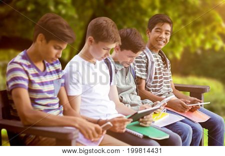 Friends using digital tablets on bench against trees and meadow in the park