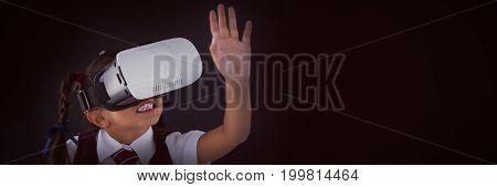 Schoolgirl using virtual reality headset against blackboard in classroom