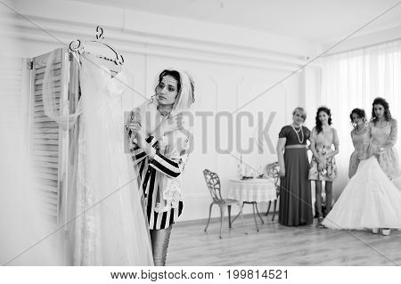 Bridesmaids And Mother Looking At Bride While She Is Dressing Up. Black And White Photo.