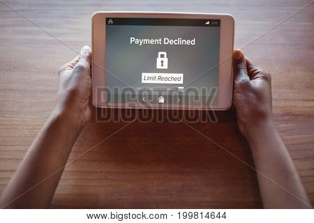 Payment declined and limit reached text on phone screen against cropped hands of woman using digital tablet
