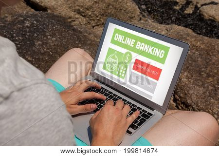 Online banking text on gray display against man sitting on the rocks and using laptop at the sea coast