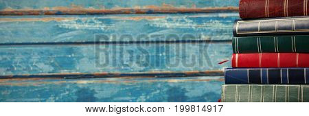 Colorful books stacked on wooden table