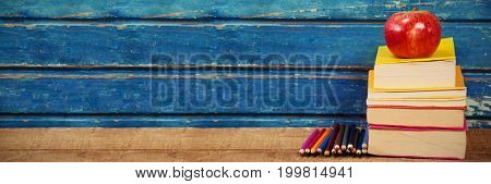Apple with stacked books and colored pencils on wooden table