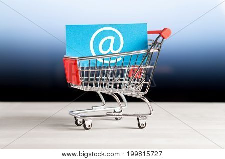 Online shopping, e commerce and internet store concept. Newsletter and email marketing. Miniature shopping cart with at sign.
