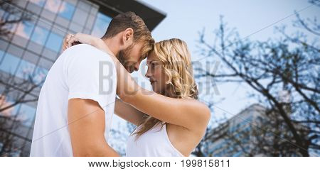 Couple cuddling against white background against trees and building against clear sky