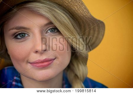 Close up portrait of smiling young blonde woman against orange background