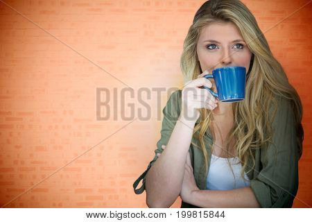 Portrait of young blonde woman against orange background