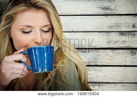 Portrait of beautiful blonde women drinking coffee against a beige wall