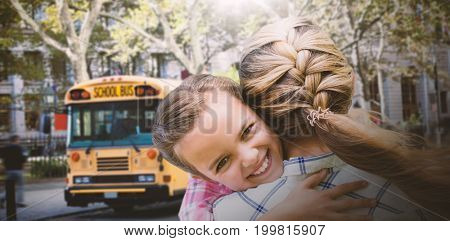 Mother and daughter hugging  against schoolbus on ny street
