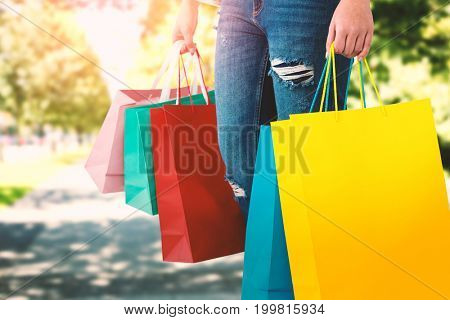 Women holding bag with blank space against blur view of park