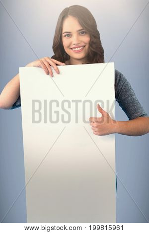 Brunette women holding blank poster against grey background