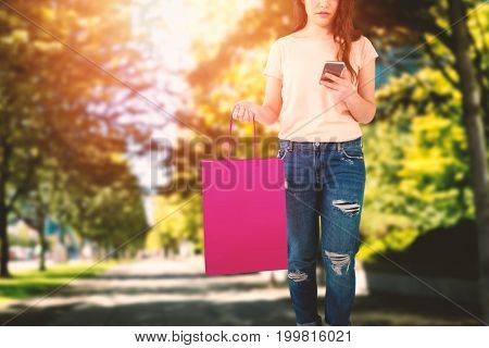 Beautiful brunette women holding bags against footpath amidst trees