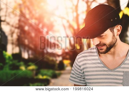 Handsome man wearing hat  against footpath by trees in city