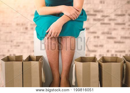 Women sitting next to bags  against stone wall