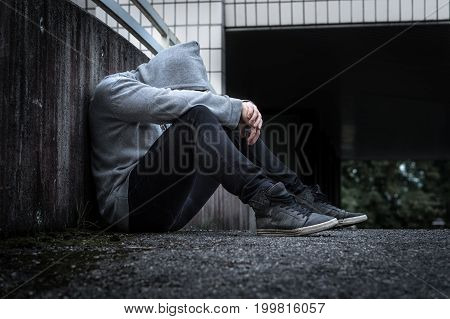 Depression, social isolation, loneliness, mental health and discrimination concept. Sad, lonely, depressed and unhappy man. Hooded person sitting in dark alley.