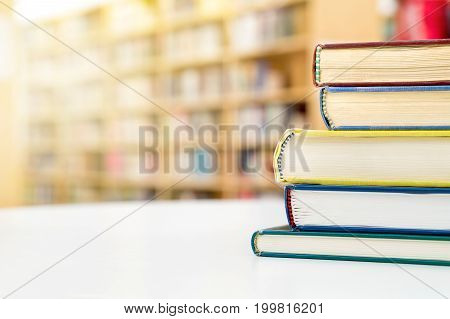 Stack and pile of books on table in public or school library. Education, studying and literature service concept with negative copy space.