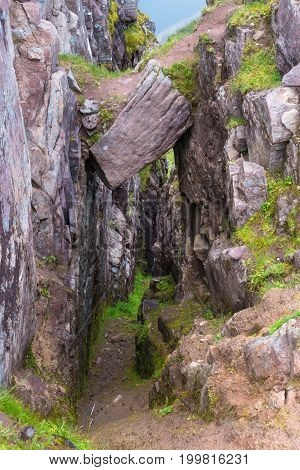 Mountain Trail Descending Into Canyon With Hanging Rock Above Entrance