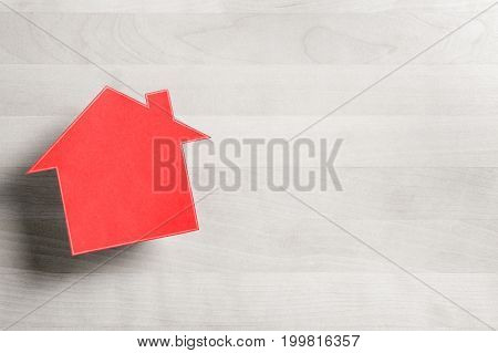 Real estate business. House for sale. Cottage made from cardboard paper on wooden table. House warming party template. Selling and buying home. Empty blank negative copy space.