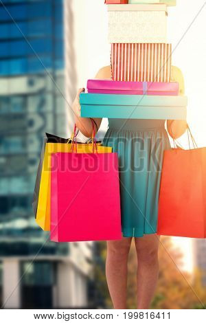 Pretty women holding shopping bags against modern buildings against sky