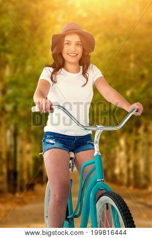 Portrait of smiling cycling woman  against walkway along lined trees in the park