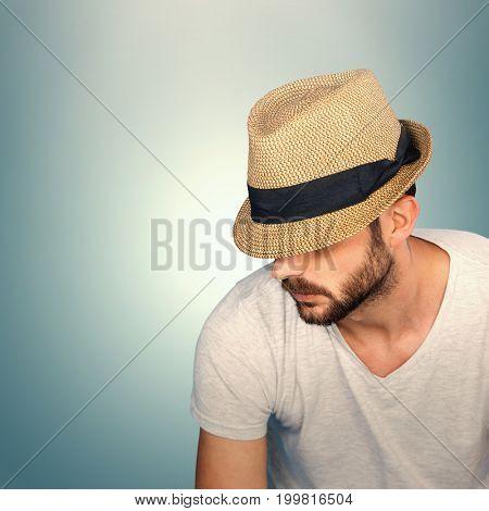 Handsome man wearing hat  against grey vignette