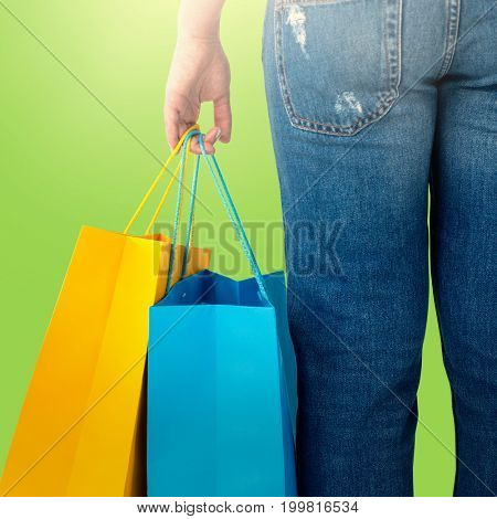 Beautiful brunette women holding bags against green background