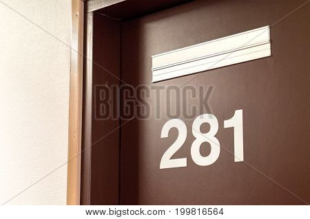 Doctor's door. The entrance to the room of a psychologist, psychiatrist, nurse or dentist in a hospital or the office of principal or curator in school. Universal door with number and empty sign.