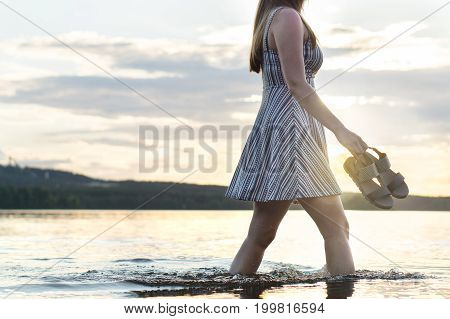 Young attractive woman walking in lake water at sunset. Carefree and happy lifestyle. Holding sandals in hand. Freedom and happiness concept. Hot summer night.