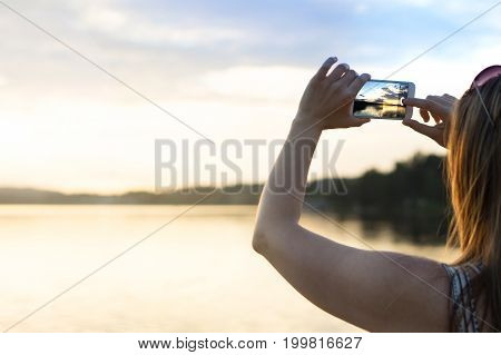 Young woman taking photo of a beautiful sunset with smart phone. Carefree summer holiday lifestyle. Travel and leisure concept. Negative space for copy.