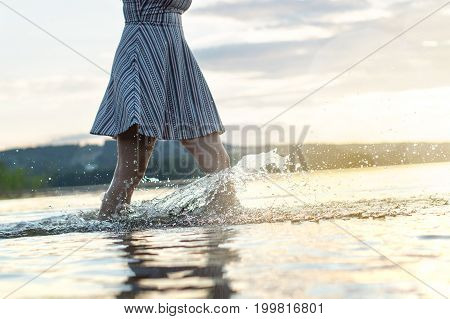 Young attractive woman in sunset. Water splashing when walking in the lake. Carefree and happy summer lifestyle. Hot summer night.