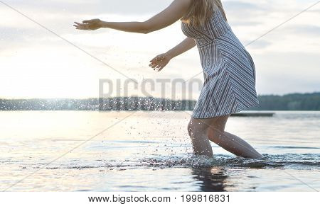 Happy beautiful young woman splashing water in lake with hands. Healthy, active and carefree lifestyle. Freedom and having fun concept. Hot summer night.