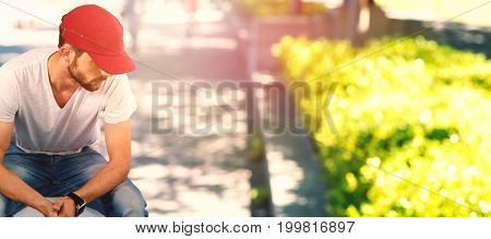 Man thinking and wearing red hat  against blur view of park