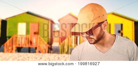 Model wearing cap and sunglasses against multi colored huts on sand against clear sky