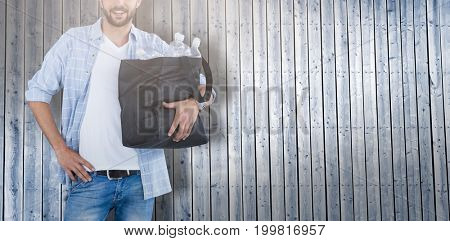 Portrait of man wearing hat carrying water bottles in bag against digitally generated grey wooden planks