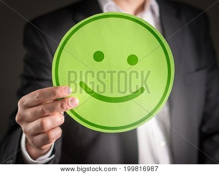Business man with happy cardboard smiley face emoticon. Customer satisfaction or successful business concept.
