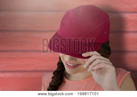 Smiling female model showing red cap against full frame shot of red wall