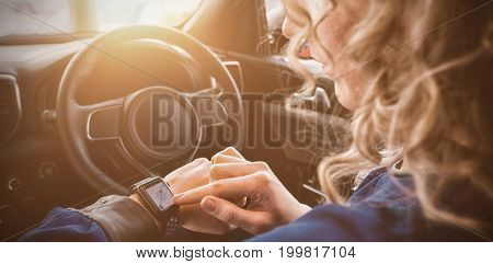 Close up of woman using smart watch in car during test drive
