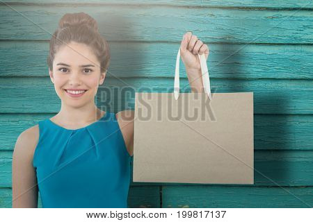 Women holding bag with blank space against full frame shot of turquoise wall