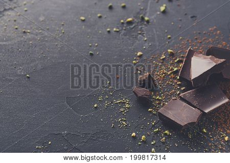Sweet background. Broken pieces of dark bitter chocolate, cocoa powder and pistachio crumble on black stone surface, copy space