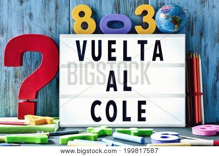 the text vuelta al cole, back to school in spanish, in a lightbox placed against a rustic wooden background, surrounded by three-dimensional numbers and chalks and pencils of different colors