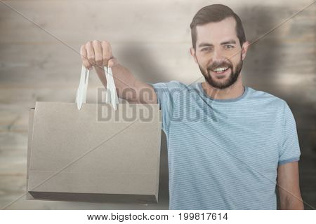 Portrait of smiling man showing shopping bag against bleached wooden planks background