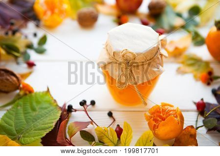 Bank Of Honey And Color Autumn Leaves On A White Wooden Background