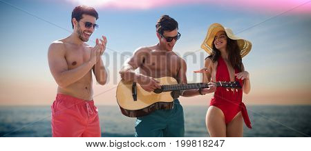 Friends playing music in swimwear against idyllic view of sea
