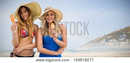 Two women eating ice cream  against beautiful beach and blue sky