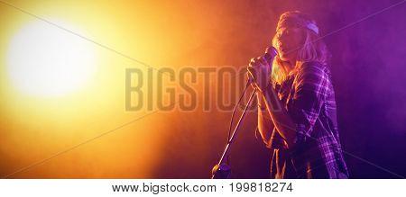 Female singer performing at concert in nightclub