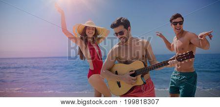 Friends playing music in swimwear against beach against clear sky