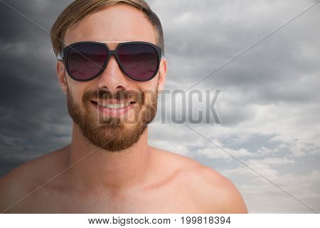 Portrait of handsome man wearing sunglasses against cloudy sky