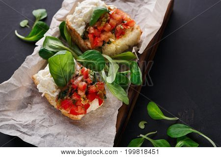 Restaurant appetizer on black background. Crusty bruschetta with concasse tomatoes, stracciatella cheese decorated with spinach. Delicious and healthy meals, copy space