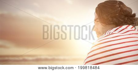 Profile view of handsome man  against view of beach during sunset