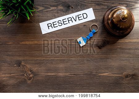 Book hotel. Word reserved near hotel service bell on dark wooden table background top view.